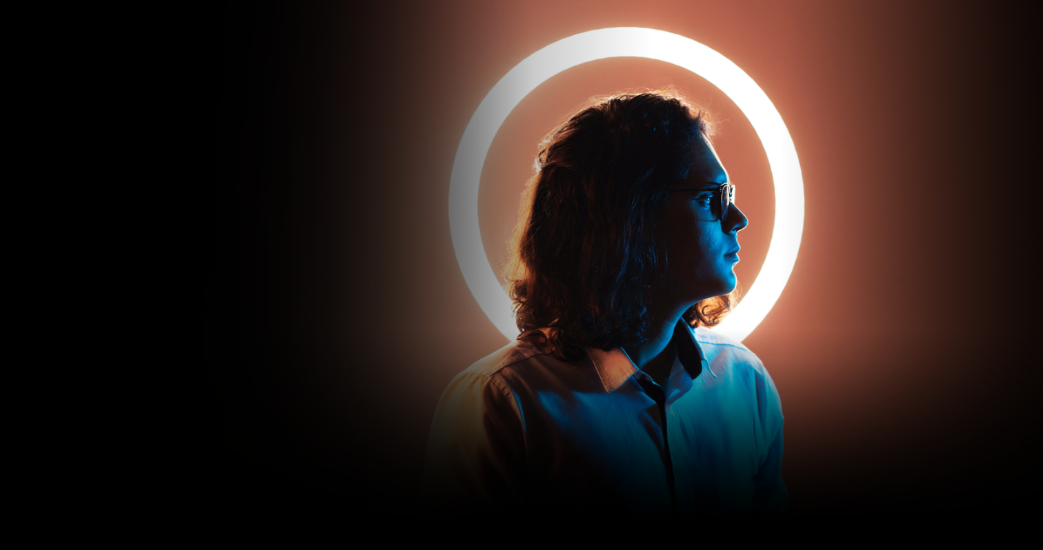Man wearing glasses standing in front of a ring light with an orange hue looking into the distance