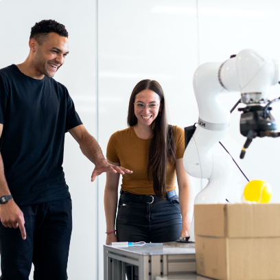 A male and female looking and smiling at a white robotic arm.