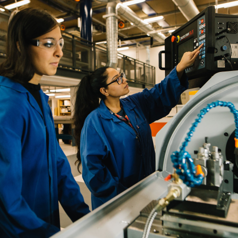 Two women wearing safety glasses and blue lab coats in an engineering workshop